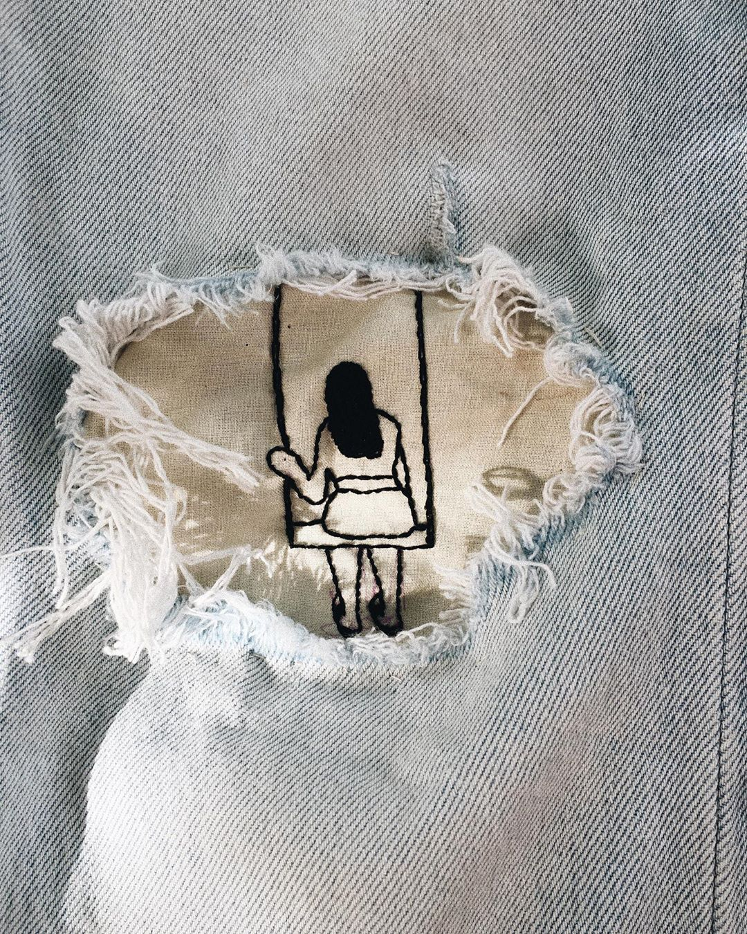 visible mending inspiration with hand embroidery, girl on a swing patched on the jeans