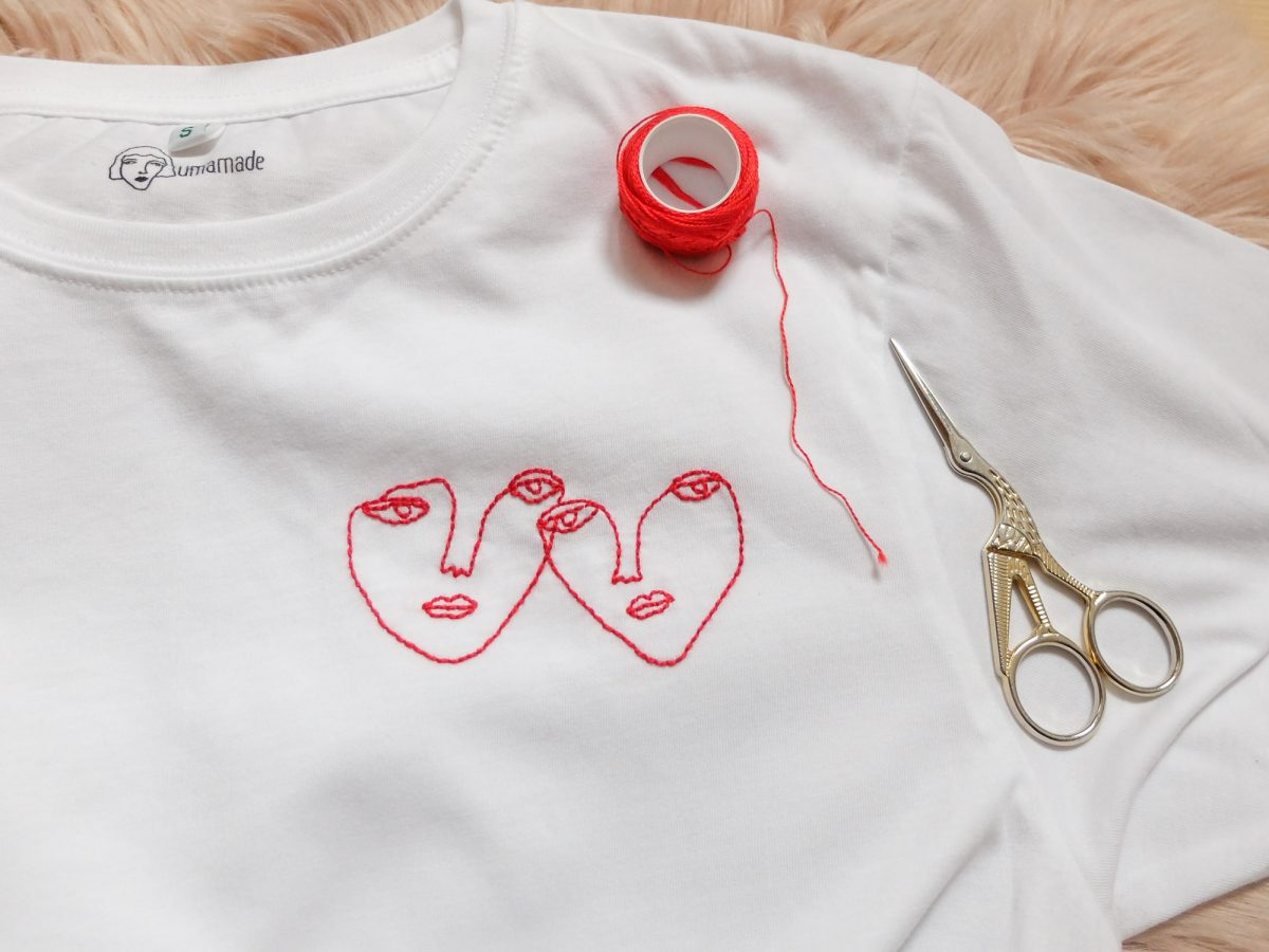 visible mending two red faces line drawing embroidered